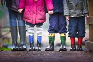 Four children standing in colourful wellingtons