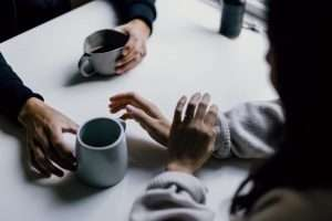 People sitting at table drinking coffee